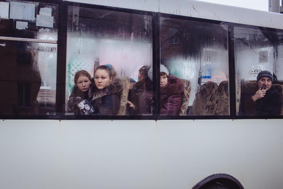 Bewohner von Donezk schauen über die Straße auf ein durch den Beschuss einer nahe gelegenen metallurgischen Fabrik beschädigtes Mehrfamilienhaus - Foto: Max Avdeev / Meduza