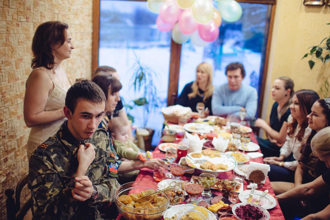 Eine Familienfeier in Makejewka bei Donezk. Sascha, 15 Jahre alt, kämpfte im Laufe des Sommers bei den Kämpfen um den Donezker Flughafen in der 15. Internationalen Brigade der Separatisten. Seine Familie feiert heute den Geburtstag seiner älteren Schwester. Die Familie ist durch und durch Mittelklasse, aber sie unterstützten aktiv Saschas Entschluss, im Krieg zu kämpfen. Viele sind ehemalige Anhänger der Maidan-Bewegung, die Menschen um den Tisch sprechen manchmal Ukrainisch. Trotz ihrer Liebe für ukrainische Kultur sagen jedoch Saschas Mutter und Vater, dass sie nicht mehr an eine vereinte Ukraine glauben. - Foto: Max Avdeev / BuzzFeed News