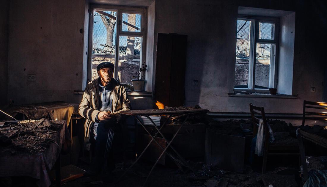 67-jährige Viktor Garashchenko sitzt in seinem zerbombten Haus. - Foto: Max Avdeev / Meduza