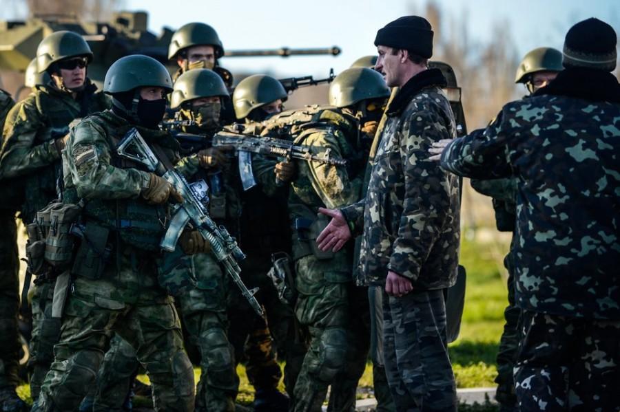 """Das Bild zeigt die """"Tapferkeit"""", für die russische Streitkräfte so ausgezeichnet werden: """"Grüne Männchen"""", bis an die Zähne bewaffnet, stehen vor dem Flughafen Belbek/Krim unbewaffneten ukrainischen Soldaten gegenüber. Es wurde in Polen als Photo des Jahres ausgezeichnet. Foto: Kuba Kaminski."""