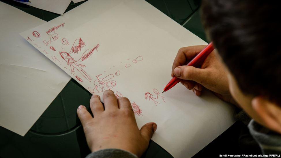 """10 - Therapie. Ein Junge soll Worte in Bilder umsetzen. Er zeichnete einen Panzer für das Wort """"Krieg""""."""