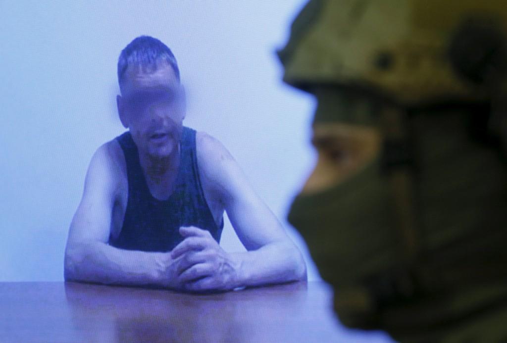 Ein Offizier des ukrainischen Geheimdienstes SBU steht während eines Briefings am 29. Juli neben einem Monitor, in dem, so der SBU, ein russischer Major zu sehen ist, der von ukrainischen Soldaten gefangengenommen wurde. - Foto: REUTERS/Valentyn Ogirenko
